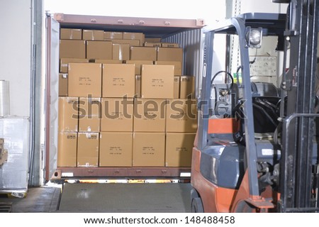 Cardboard boxes and fork lift truck in distribution warehouse - stock photo