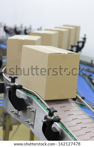 Cardboard boxes on conveyor belt in factory  - stock photo