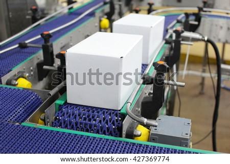 Cardboard boxes on conveyor belt in factory - stock photo