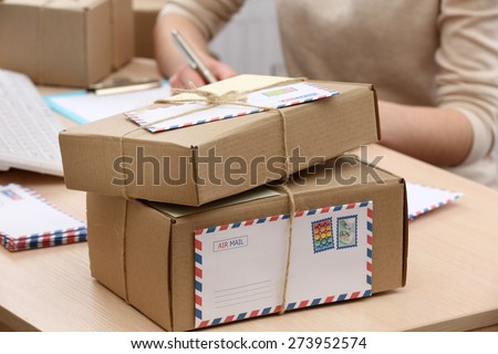 Cardboard boxes on work place in post office - stock photo