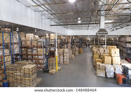 Cardboard boxes stacked in distribution warehouse - stock photo