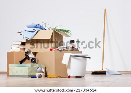 Cardboard boxes with a broom, a shovel and tools on a wooden floor  - stock photo