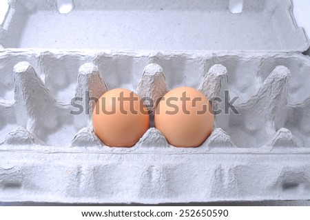 Cardboard egg box with brown egg isolated with clipping path - stock photo