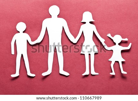 Cardboard figures of the family on a red background. The symbol of unity and happiness.