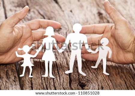 Cardboard figures of the family on a wooden table. The symbol of unity and happiness. Hands gently hug the family. - stock photo