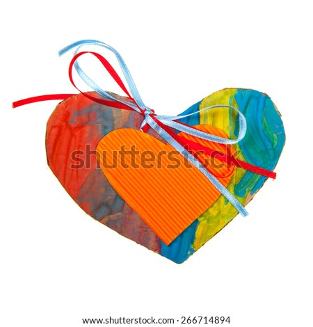Cardboard heart with blue and red ribbons isolated over white - stock photo