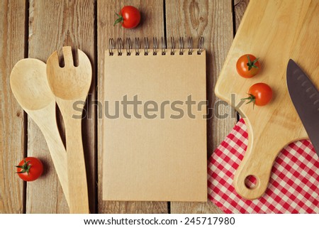 Cardboard notepad with kitchen utensils on wooden table. View from above - stock photo