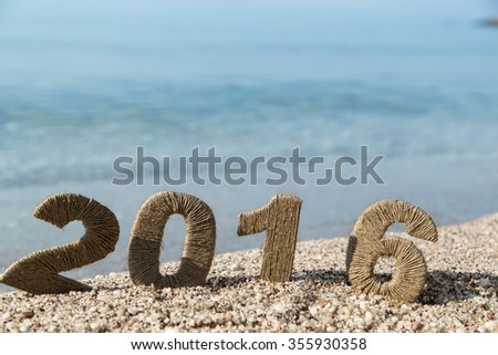 Cardboard numbers 2016 covered with rope placed on a beautiful beach with seascape in the background - stock photo
