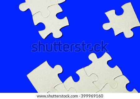 cardboard puzzles pieces on a blue background - stock photo
