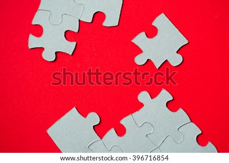 cardboard puzzles pieces on a red background - stock photo