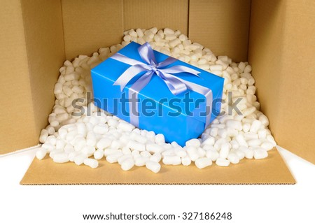 Cardboard shipping delivery box open with blue gift inside and polystyrene packing pieces. - stock photo