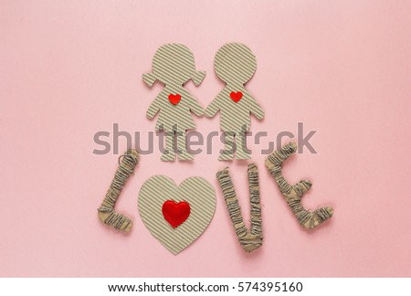 Cardboard silhouettes girl and boy with hearts and the word love on a pink background. Valentine's Day background. Top view.