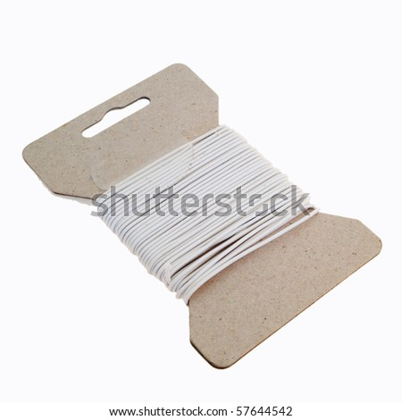 Cardboard with several windings of an elastic thread isolated on white - stock photo