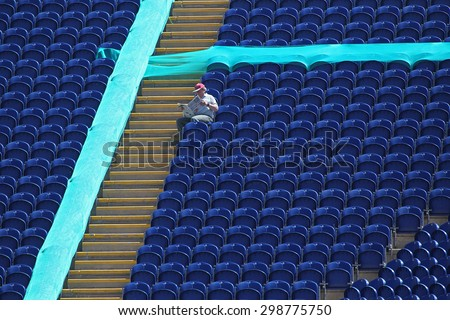 CARDIFF, WALES - June 04 2013: A lone fan sits in the stand reading a newspaper during the ICC Champions Trophy warm up match between India and Australia at the Cardiff Wales Stadium