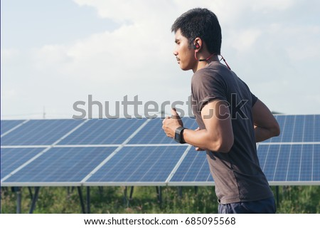 Cardio runner running listening smartphone music in a solar power plant. Sporty fit young man jogging,Exercising, fitness and healthy lifestyle concept