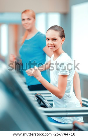 Cardio training. Side view of beautiful mature woman and her daughter in sports clothing having a workout on a treadmill in the gym