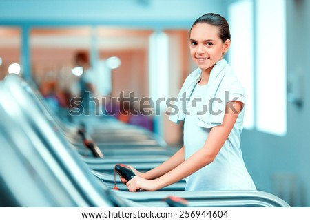 Cardio training. Side view of beautiful teen girl n in sports clothing and towel on her shoulders smiling after her workout on a treadmill in the gym  - stock photo