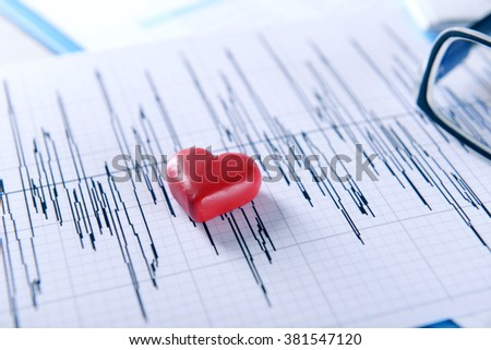 Cardiogram chart with glasses and small red heart on table closeup