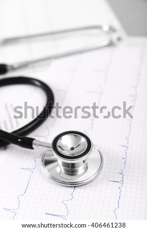 Cardiogram chart with medical stethoscope on table closeup - stock photo