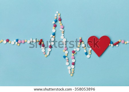 Cardiogram is made of colorful drug pills and red paper heart, pharmaceutical and cardiology concept