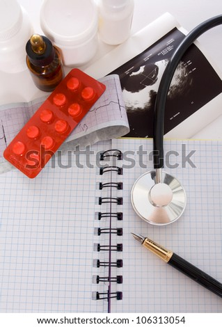 Cardiogram of the heart, stethoscope and pills - stock photo