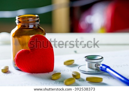 Cardiogram with stethoscope, pill and red heart on table, closeup