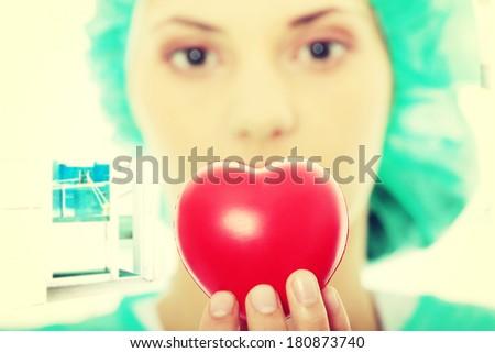 Cardiologist holding heart - focus on heart - stock photo