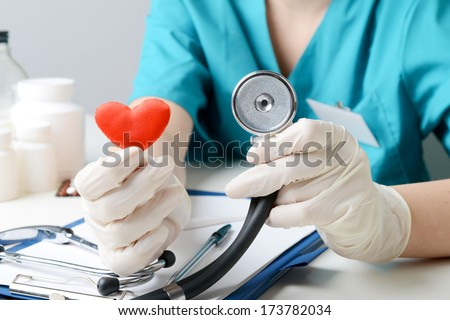 cardiologist sitting in an office in the hospital and shows heart and stethoscope, medical concept - stock photo