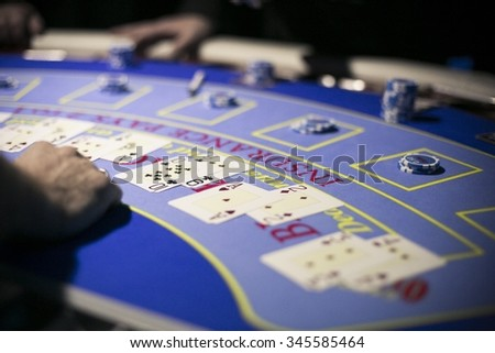 Cards and chips laid in front of the dealer on the black jack table in a casino - stock photo