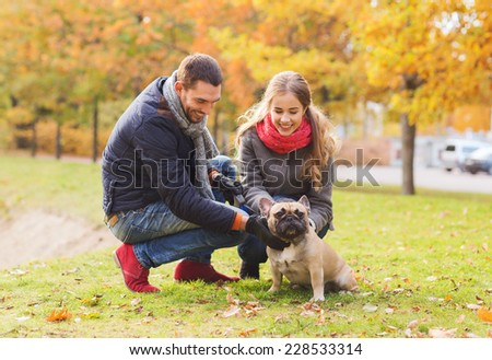 care, animals, family, season and people concept - smiling couple with dog in autumn park - stock photo