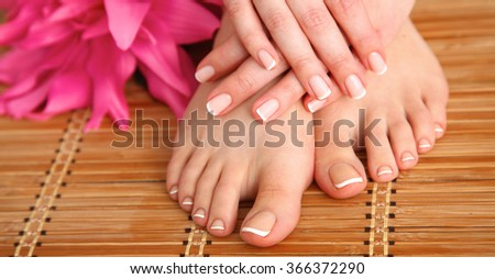 Care for beautiful woman legs with flower - stock photo