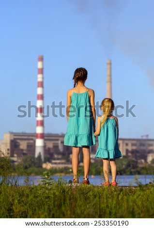 care future concept. sisters are looking at the chimney-stalks polluting an air  - stock photo