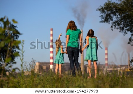 care future concept. Young mother with her kids are looking at the chimney-stalks polluting an air  - stock photo