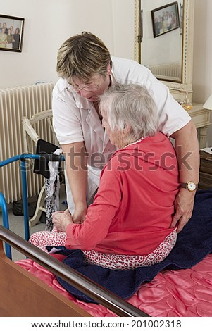 Care giver helping elderly woman to dress at home - stock photo