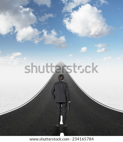 Career development business concept. Businessman is standing on the highway leading to an arrow.  - stock photo