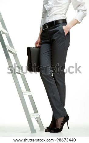 Career ladder: businesswoman starting career; ladder of success concept, white background - stock photo