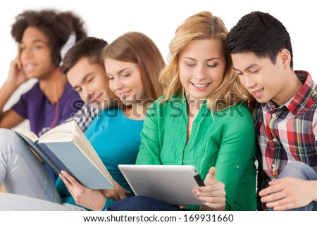 Carefree and young. Group of multi-ethnic students spending time together while sitting isolated on white - stock photo