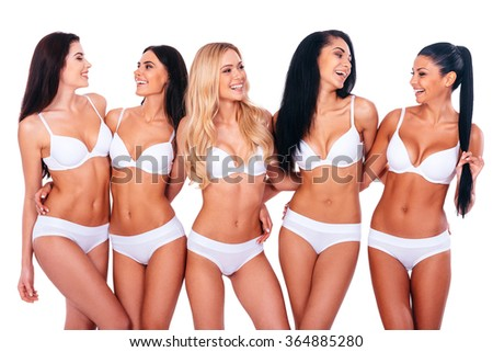 Carefree beauties. Group of cheerful women in lingerie embracing and looking at each other while standing against white background - stock photo
