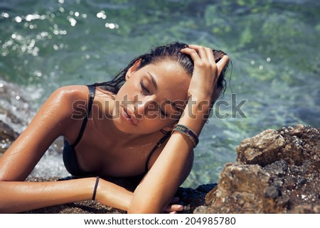 Carefree beautiful brunette with wet look and bright makeup by the sea. Toned in warm colors. horizontal shot, outdoors - stock photo