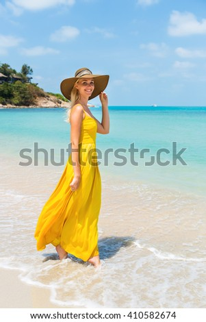 Carefree beautiful fashion blonde female in beach straw hat walking barefoot by sand of tropical shore and holding her long yellow dress. Natural woman beauty. Lady touch her hat and smiles. - stock photo
