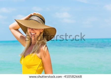 Carefree beautiful fashion blonde woman in beach straw hat and long yellow dress flying in the wind at the tropical beach seashore. Natural woman beauty. Lady hold her hat and smile to the camera. - stock photo