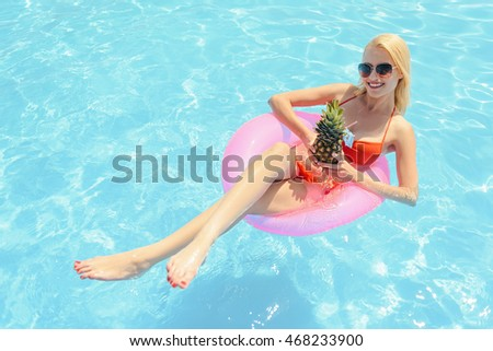 Carefree blond woman enjoying drink on vacation