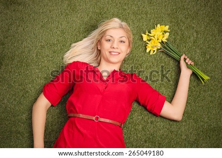 Carefree blond woman lying in a green field and holding a bunch of yellow tulips  - stock photo