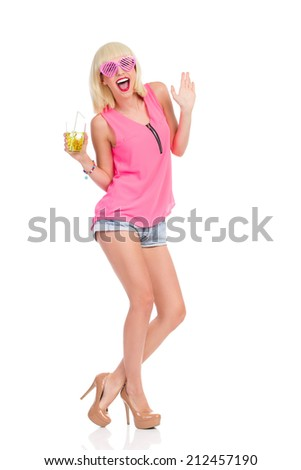 Carefree blond young woman in high heels, pink top and jeans shorts dancing and holding lime drink. Full length studio shot isolated on white. - stock photo