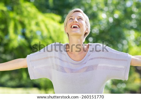 Carefree blonde in a park on a sunny day - stock photo