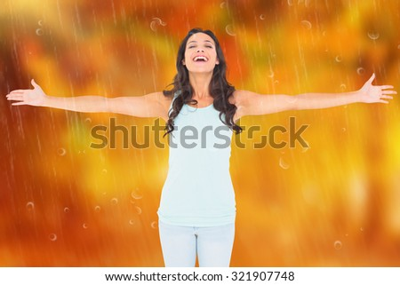 Carefree brunette with arms out against autumn scene - stock photo
