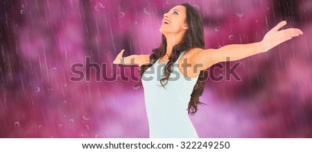 Carefree brunette with arms out against path in autumnal forest - stock photo