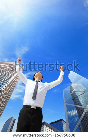 carefree business man arms up and looking to empty copy space with business building background, asian model, hong kong - stock photo