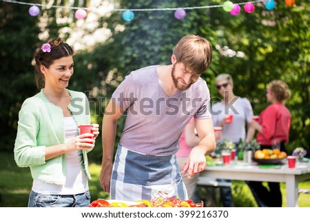 Carefree couple enjoying themselves at barbecue party - stock photo