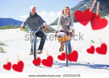 Carefree couple going for a bike ride and picnic on the beach against hearts hanging on a line - stock photo